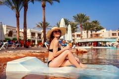Donna che si rilassa nella piscina dell'hotel che si trova sulle chaise longue con il cocktail Vacanza di estate Tutto l'incluso immagini stock