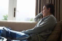 Donna che si rilassa su Sofa In Living Room Immagine Stock