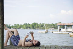 Donna che si rilassa su una lettura del molo Fotografia Stock