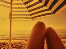 Donna che si rilassa su una spiaggia con l'ombrello coloritura d'annata di tramonto di seppia romantica della sabbia alla retro Fotografia Stock