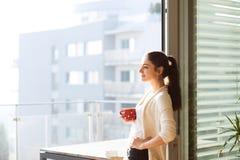 Donna che si rilassa sul balcone che tiene tazza di caffè o tè immagini stock