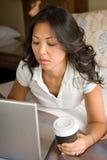 Donna che si rilassa sul letto facendo uso del computer portatile Immagini Stock Libere da Diritti