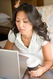 Donna che si rilassa sul letto facendo uso del computer portatile Fotografia Stock