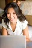 Donna che si rilassa sul letto facendo uso del computer portatile Immagini Stock