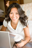 Donna che si rilassa sul letto facendo uso del computer portatile Fotografie Stock Libere da Diritti