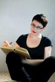 Donna che si rilassa sul libro di lettura del pavimento a casa Fotografia Stock