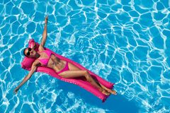 Donna che si rilassa sul materasso di aria nella piscina Immagini Stock