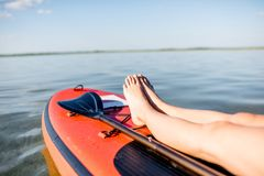 Donna che si rilassa sul paddleboard fotografia stock