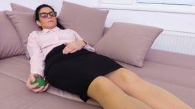 Donna che si rilassa sul sofà e che schiaccia la palla di sforzo archivi video