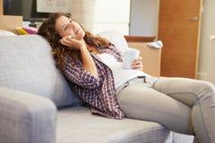 Donna che si rilassa sulla nuova casa di Sofa Talking On Phone In Immagini Stock