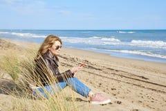Donna che si rilassa sulla spiaggia con il suo telefono cellulare Immagine Stock