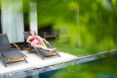 Donna che si rilassa sulle chaise longue vicino allo stagno. Fotografia Stock Libera da Diritti
