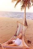 Donna che si rilassa in un'amaca su una spiaggia fotografia stock libera da diritti