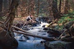 Donna che si rilassa vicino al fiume della montagna in foresta verde Immagini Stock