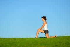 Donna che si scalda il giunto di ginocchio prima dell'correre Fotografia Stock