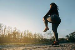 Donna che si scalda le gambe prima del funzionamento all'aperto Immagine Stock Libera da Diritti