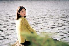 Donna che si siede accanto ad un fiume Fotografia Stock