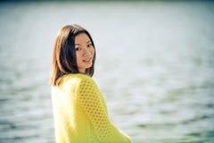 Donna che si siede accanto ad un fiume Fotografia Stock Libera da Diritti