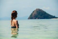 Donna che si siede in acqua che esamina isola Immagine Stock
