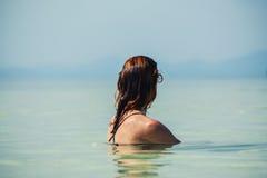 Donna che si siede in acqua dalla spiaggia Immagine Stock