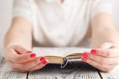 Donna che si siede ad una tavola che legge un libro Immagine Stock Libera da Diritti