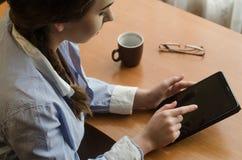 Donna che si siede ad una tavola con una compressa Fotografia Stock