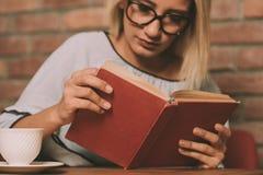 Donna che si siede ad una tavola che legge un libro Fotografia Stock