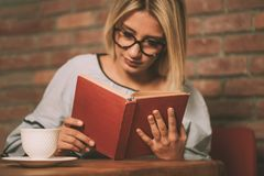 Donna che si siede ad una tavola che legge un libro Fotografie Stock
