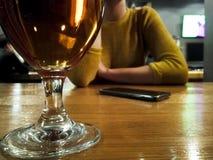 Donna che si siede al contatore della barra, vetro di birra dentro da a fuoco Immagini Stock