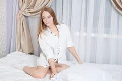Donna che si siede al letto Immagine Stock Libera da Diritti