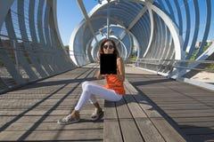Donna che si siede al posto moderno in città che mostra lo schermo della compressa Immagini Stock Libere da Diritti
