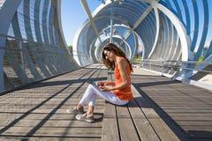 Donna che si siede al posto moderno in Internet praticante il surfing della città in compressa Fotografia Stock