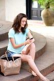 Donna che si siede all'aperto con il telefono cellulare Immagini Stock Libere da Diritti