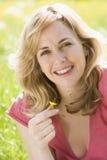 Donna che si siede all'aperto tenendo sorridere del fiore Fotografie Stock Libere da Diritti
