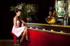 Donna che si siede alla barra Fotografia Stock