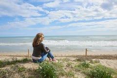 Donna che si siede alla spiaggia Immagine Stock Libera da Diritti