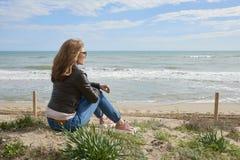 Donna che si siede alla spiaggia Fotografia Stock Libera da Diritti