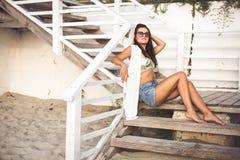 Donna che si siede alla spiaggia Immagini Stock Libere da Diritti