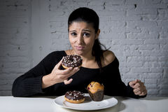 Donna che si siede alla tavola che ritiene colpevole dimenticando dieta che mangia piatto in pieno dell'alimento non sano zuccher fotografia stock