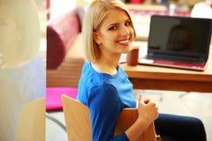 Donna che si siede alla tavola con il computer portatile Immagini Stock Libere da Diritti