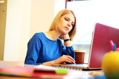 Donna che si siede alla tavola con il computer portatile Fotografia Stock