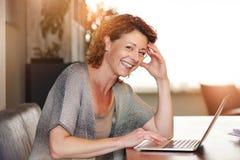 Donna che si siede alla tavola con sorridere con il computer portatile Fotografie Stock Libere da Diritti