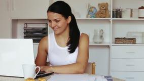 donna che si siede alla tavola e che lavora al computer portatile video d archivio