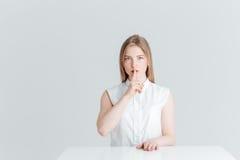 Donna che si siede alla tavola e che mostra dito sopra le labbra Fotografie Stock