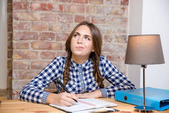 Donna che si siede alla tavola e che pensa al suo compito Immagine Stock Libera da Diritti