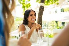 Donna che si siede alla tavola in ristorante all'aperto Immagini Stock Libere da Diritti