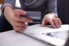 Donna che si siede allo scrittorio, comperante con il computer portatile Fotografia Stock Libera da Diritti