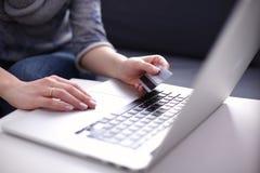 Donna che si siede allo scrittorio, comperante con il computer portatile Immagine Stock Libera da Diritti