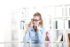 Donna che si siede allo scrittorio con il telefono cellulare Immagine Stock Libera da Diritti