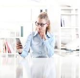 Donna che si siede allo scrittorio con il telefono cellulare Fotografia Stock